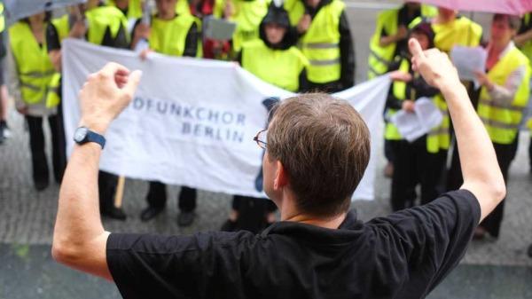 Simon Halsey dirigiert den Rundfunkchor Berlin vor der Komischen Oper